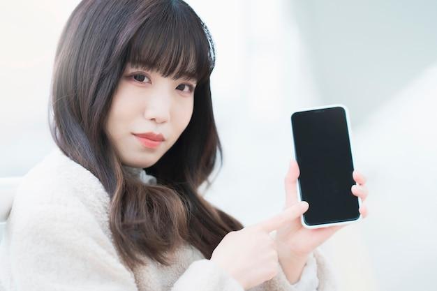Aziatische jonge vrouw die op het scherm let en een smartphone bedient