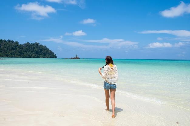 Aziatische jonge vrouw die op wit strand in smaragdgroene overzees loopt