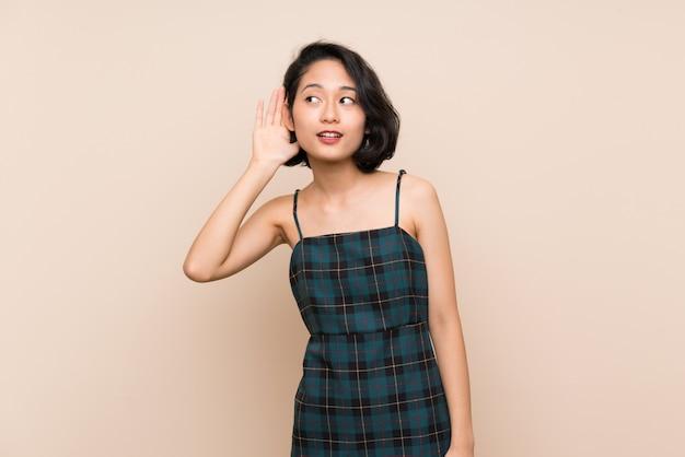 Aziatische jonge vrouw die over geïsoleerde gele muur aan iets door hand op het oor te zetten luistert