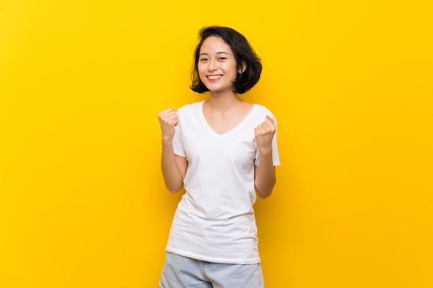Aziatische jonge vrouw die over geïsoleerde gele muur een overwinning in winnaarpositie viert