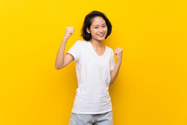 Aziatische jonge vrouw die over geïsoleerde gele muur een overwinning viert
