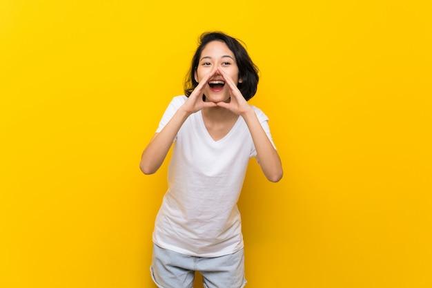 Aziatische jonge vrouw die over geïsoleerde gele muur en iets schreeuwen aankondigen