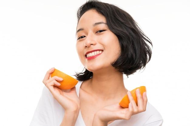 Aziatische jonge vrouw die over geïsoleerde muur een sinaasappel houdt