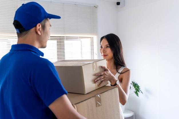 Aziatische jonge vrouw die pakket ontvangt van de leveringsman