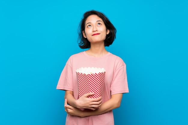 Aziatische jonge vrouw die popcorn eet die omhoog terwijl het glimlachen kijkt