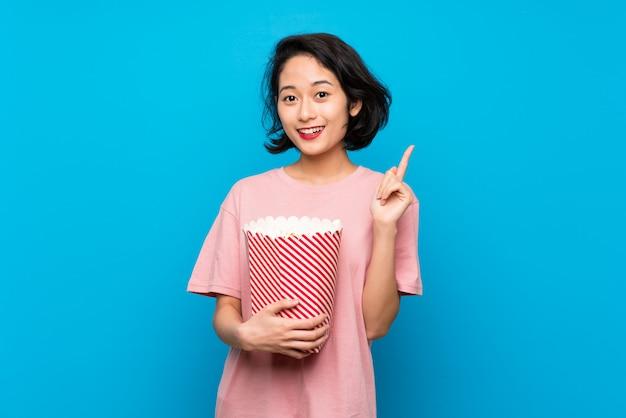 Aziatische jonge vrouw die popcorns eet die een groot idee benadrukken