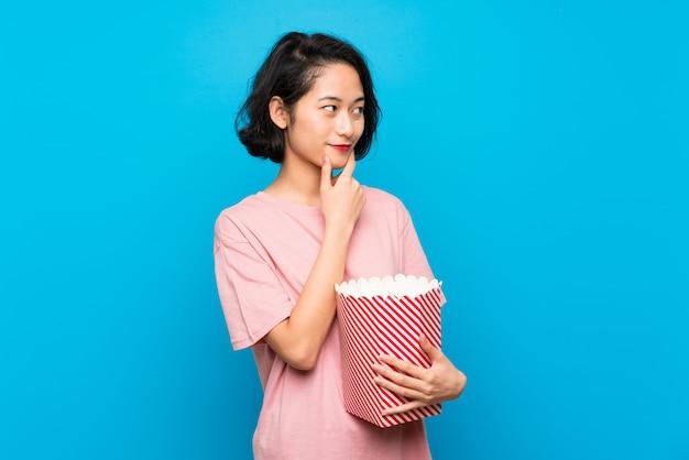 Aziatische jonge vrouw die popcorns eet die een idee denkt