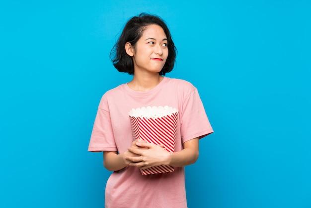 Aziatische jonge vrouw die popcorns eet die twijfelsgebaar maken terwijl het opheffen van de schouders