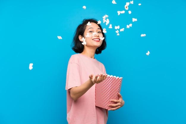 Aziatische jonge vrouw die popcorns eet