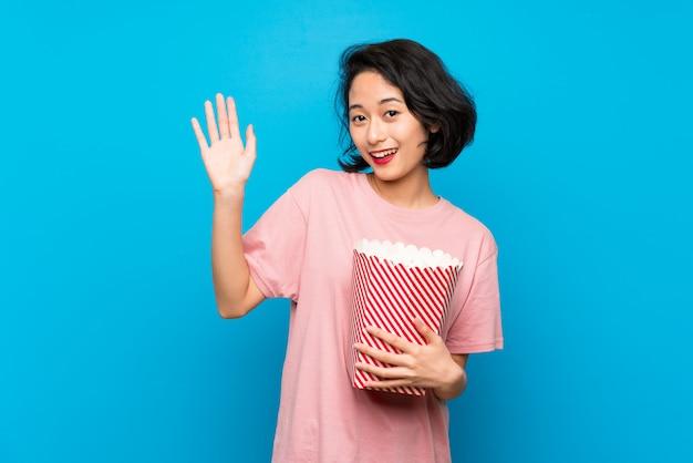 Aziatische jonge vrouw die popcorns eten die met hand met gelukkige uitdrukking groeten