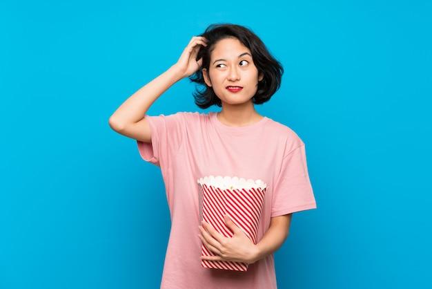 Aziatische jonge vrouw die popcorns eten die twijfels hebben en met verwarren gezichtsuitdrukking
