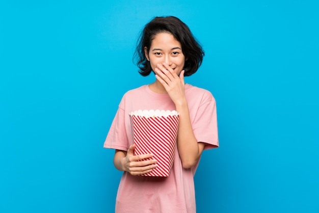 Aziatische jonge vrouw die popcorns met verrassingsgelaatsuitdrukking eet