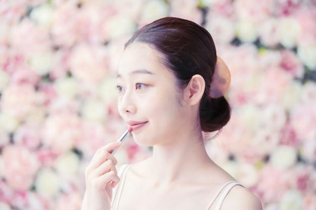 Aziatische jonge vrouw die rode lippenstift op haar lippen zet
