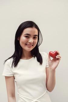 Aziatische jonge vrouw die rood hart, ziekteverzekering, schenkingsconcept houdt
