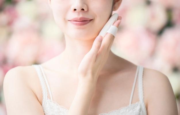 Aziatische jonge vrouw die rookwolk zet aan haar gezichtshuid