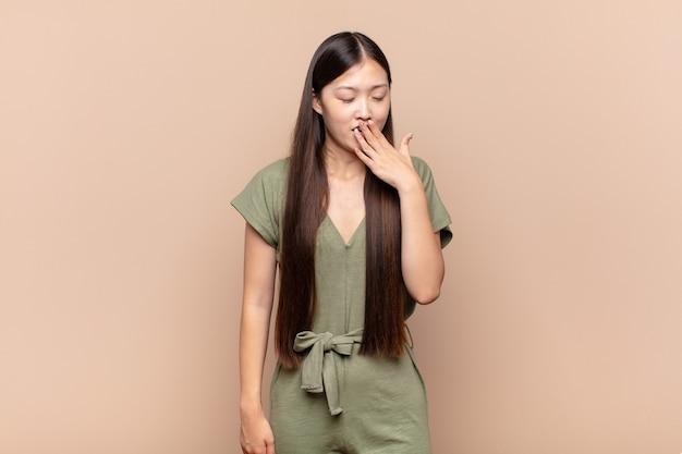 Aziatische jonge vrouw die 's morgens vroeg lui geeuwt, wakker wordt en er slaperig, moe en verveeld uitziet