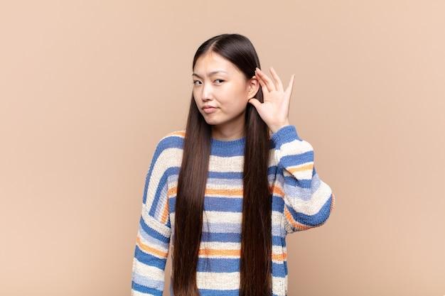 Aziatische jonge vrouw die serieus en nieuwsgierig kijkt, luistert, probeert een geheim gesprek of roddel te horen, afluisteren