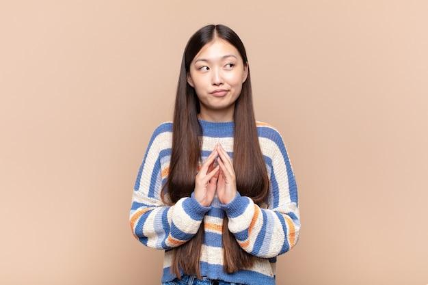 Aziatische jonge vrouw die sluw en samenzweert, sluwe trucs en bedriegers denkt, sluw en verraadt