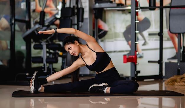 Aziatische jonge vrouw die sportkleding en smartwatch draagt die op de vloer zit en haar benen en armen uitrekt voordat ze gaat trainen in de fitnessgym