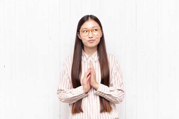 Aziatische jonge vrouw die trots, ondeugend en arrogant geïsoleerd voelt