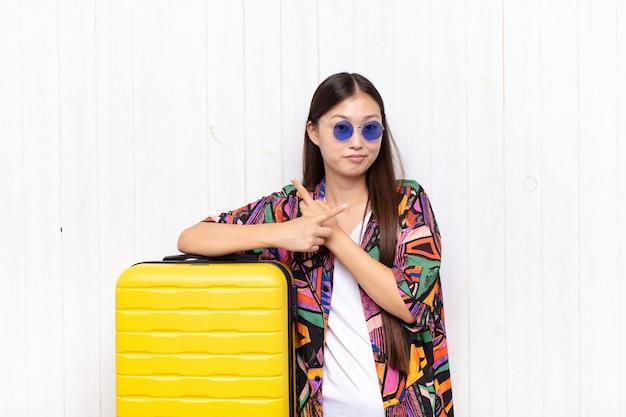 Aziatische jonge vrouw die verbaasd en verward, onzeker en met twijfels in tegengestelde richtingen kijkt. vakantie concept