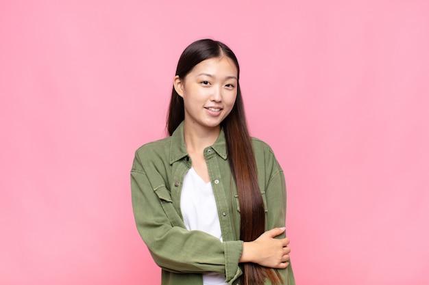 Aziatische jonge vrouw die verlegen en opgewekt lacht, met een vriendelijke en positieve maar onzekere houding