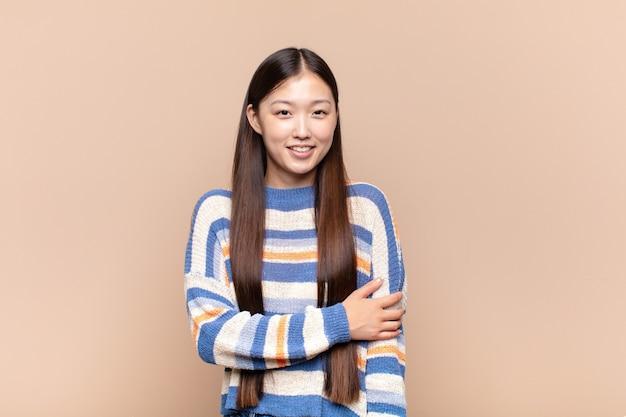 Aziatische jonge vrouw die verlegen en vrolijk geïsoleerd lacht