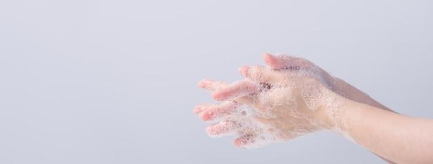 Aziatische jonge vrouw die vloeibare zeep gebruikt om handen te wassen