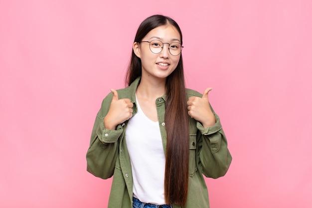 Aziatische jonge vrouw die vreugdevol glimlacht en er gelukkig uitziet, zich zorgeloos en positief voelt met beide duimen omhoog