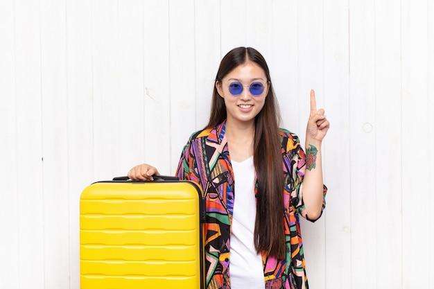 Aziatische jonge vrouw die vrolijk en gelukkig lacht en met één hand naar boven wijst om ruimte te kopiëren