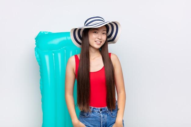 Aziatische jonge vrouw die vrolijk en terloops glimlacht met een positieve, gelukkige, zelfverzekerde en ontspannen uitdrukking. zomer concept