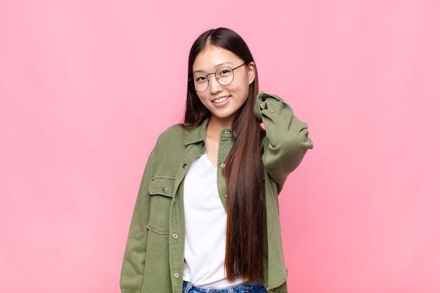 Aziatische jonge vrouw die vrolijk en vol vertrouwen lacht met een ongedwongen, gelukkige, vriendelijke glimlach