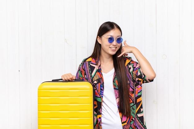 Aziatische jonge vrouw die vrolijk glimlacht en naar camera richt terwijl het u later gebaren maakt, pratend aan de telefoon