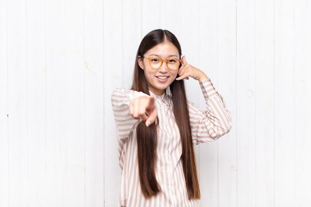 Aziatische jonge vrouw die vrolijk glimlacht en naar voren wijst terwijl het u later gebaren maakt, pratend aan de telefoon