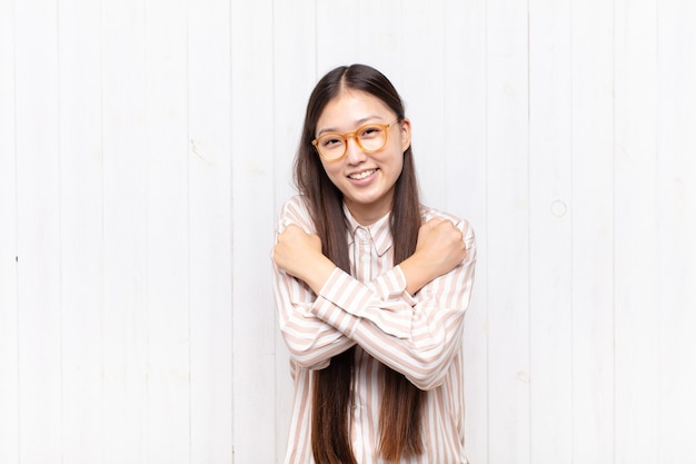 Aziatische jonge vrouw die vrolijk glimlacht en viert, met gebalde vuisten en gekruiste wapens, zich gelukkig en positief voelt