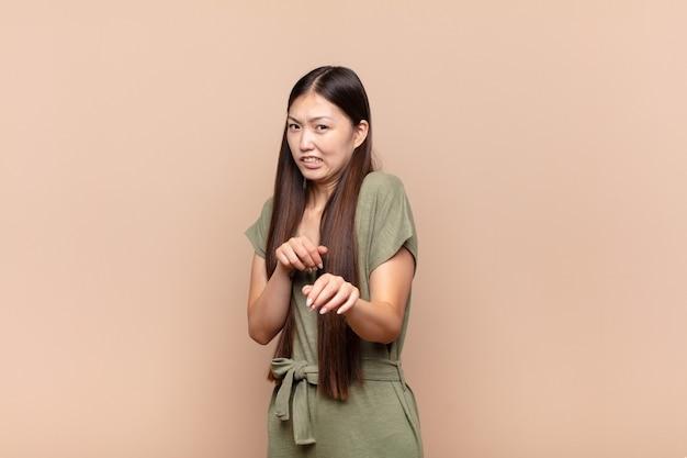 Aziatische jonge vrouw die walgt en misselijk voelt, zich terugtrekt van iets smerigs, stinkende of stinkende, bah zegt