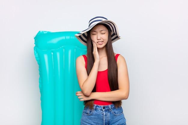 Aziatische jonge vrouw die wang houdt en pijnlijke kiespijn lijdt, zich ziek, ellendig en ongelukkig voelt, op zoek naar een tandarts. zomer concept