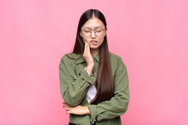 Aziatische jonge vrouw die wang vasthoudt en pijnlijke kiespijn lijdt, zich ziek, ellendig en ongelukkig voelt, op zoek naar een tandarts