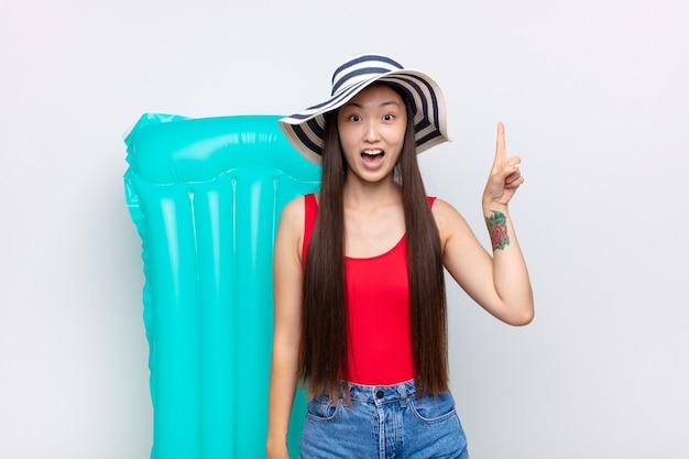 Aziatische jonge vrouw die zich als een gelukkig en opgewonden genie voelt na het realiseren van een idee, vrolijk de vinger opheffend, eureka !. zomer concept