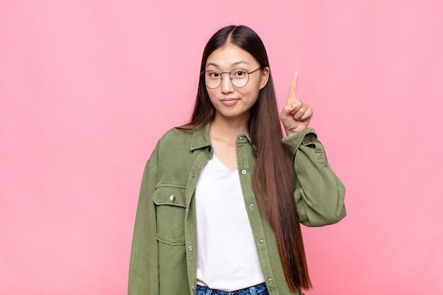 Aziatische jonge vrouw die zich als een genie voelt die de vinger trots in de lucht houdt na het realiseren van een geweldig idee