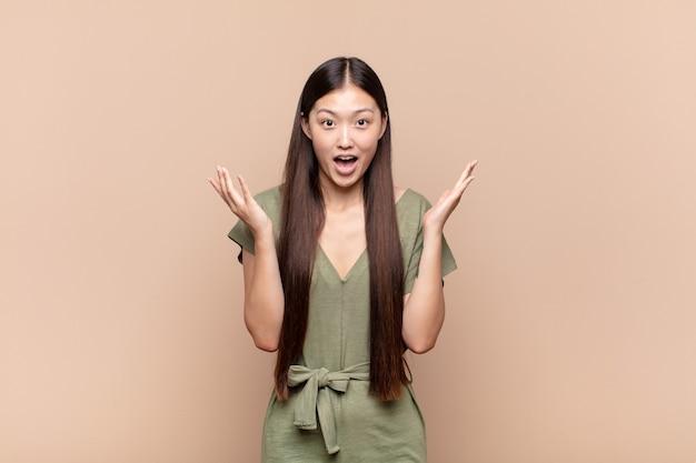 Aziatische jonge vrouw die zich blij, opgewonden, verrast of geschokt voelt, glimlacht en verbaasd is over iets ongelooflijks