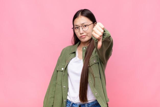 Aziatische jonge vrouw die zich boos, boos, geïrriteerd, teleurgesteld of ontevreden voelt, duimen naar beneden toont met een serieuze blik