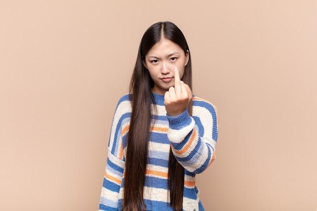 Aziatische jonge vrouw die zich boos, geïrriteerd, opstandig en agressief voelt, de middelvinger omdraait, terugvecht