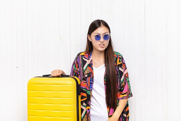 Aziatische jonge vrouw die zich geen idee, verward en onzeker voelt over welke optie ze moet kiezen, in een poging het probleem op te lossen.