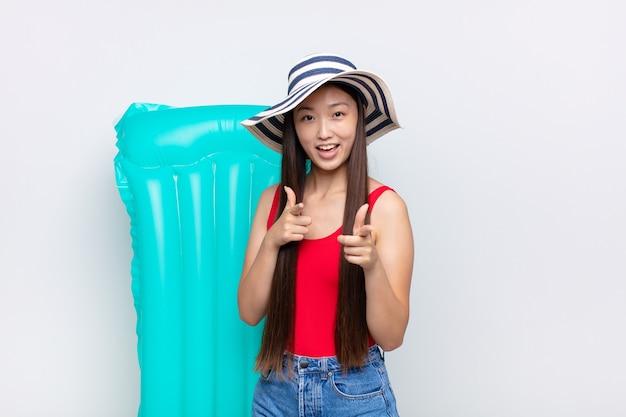 Aziatische jonge vrouw die zich gelukkig, koel, tevreden, ontspannen en succesvol voelt, wijst, jou kiest. zomer concept