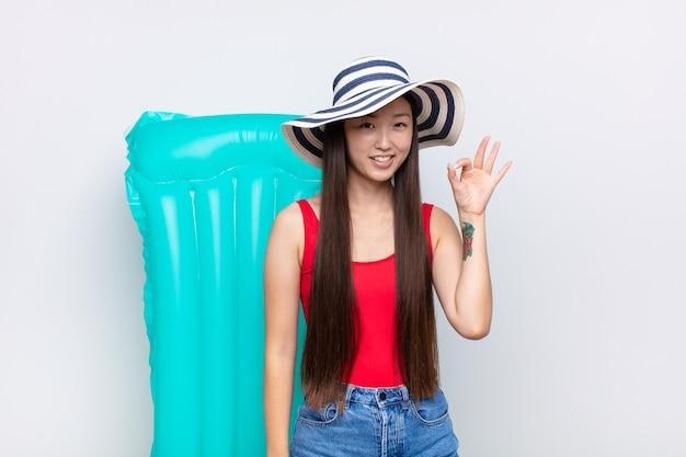 Aziatische jonge vrouw die zich gelukkig, ontspannen en tevreden voelt, goedkeuring toont met ok gebaar, glimlachend. zomer concept