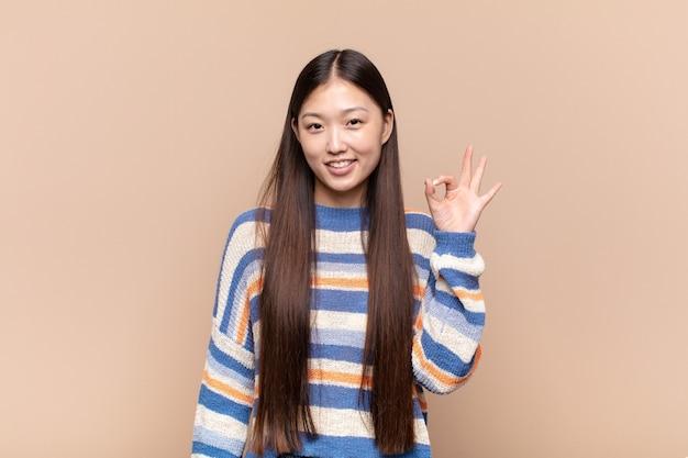 Aziatische jonge vrouw die zich gelukkig, ontspannen en tevreden voelt, goedkeuring toont met ok gebaar, glimlachend
