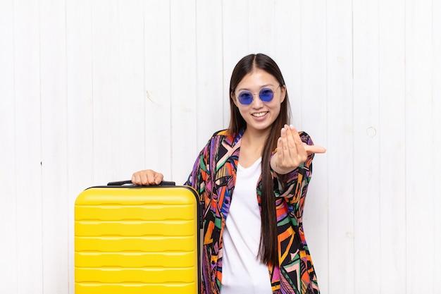 Aziatische jonge vrouw die zich gelukkig, succesvol en zelfverzekerd voelt, een uitdaging aangaat en zegt: kom maar op! of je verwelkomen. vakantie concept