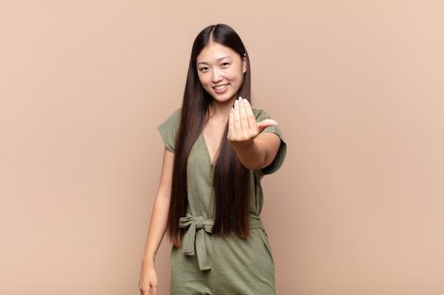 Aziatische jonge vrouw die zich gelukkig, succesvol en zelfverzekerd voelt, een uitdaging aangaat en zegt: kom maar op! of je verwelkomen