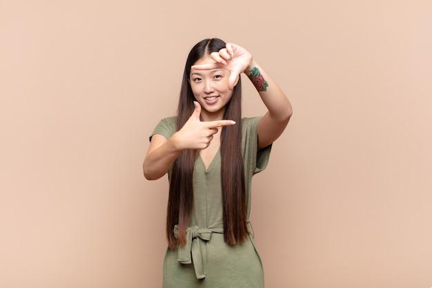 Aziatische jonge vrouw die zich gelukkig, vriendelijk en positief voelt, lacht en een portret of fotolijst met handen maakt